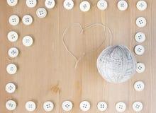 Marco de los botones del vintage y bola de costura del hilo en forma de corazón de lino en el centro Endecha plana, visión superi Fotografía de archivo