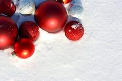 Marco de los bulbos de la Navidad en la nieve Foto de archivo