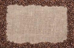 Marco de los granos de café en encendedor de la arpillera fotografía de archivo libre de regalías