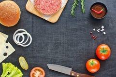 Marco de los ingredientes de la hamburguesa en una tabla negra Foto de archivo libre de regalías