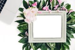 Marco de madera adornado con las flores y hojas, ordenador portátil y teléfono Espacio vacío para el texto Fotografía de archivo libre de regalías