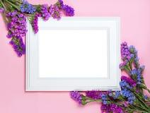 Marco de madera blanco en el fondo rosado adornado con las flores brillantes, espacio en blanco para un texto Visión superior, en Imágenes de archivo libres de regalías