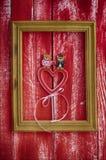 Marco de madera con el corazón de madera tallado dentro Foto de archivo