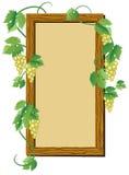 Marco de madera con la uva Imagen de archivo libre de regalías