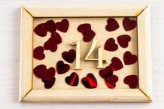 Marco de madera con los cuadros uno y cuatro y corazones en una tabla de madera blanca El símbolo del día de amantes Día de tarje Fotografía de archivo libre de regalías