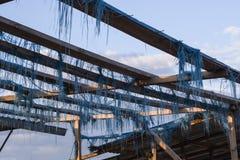 Marco de madera con los pedazos finos de tela azul rasgada en un mercado abandonado en el fondo del cielo con las nubes, Ucrania Imágenes de archivo libres de regalías