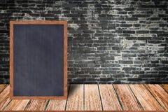 Marco de madera de la pizarra, menú de la muestra de la pizarra en la tabla de madera y fondo de la pared de ladrillo fotos de archivo