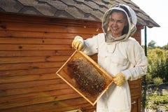 Marco de madera del control femenino joven del apicultor con el panal Recoja la miel Concepto de la apicultura foto de archivo