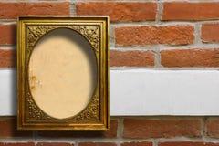 Marco de madera dorado para las imágenes en la pared de ladrillo vieja Fotografía de archivo libre de regalías