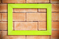 Marco de madera en blanco verde en la pared de ladrillo Imágenes de archivo libres de regalías