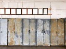 Marco de madera marrón antiguo de la foto en la pared sucia sobre los gabinetes de acero viejos foto de archivo