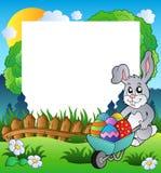 Marco de Pascua con el conejito y la carretilla Imagen de archivo libre de regalías