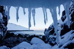 Marco del arte de los carámbanos fríos de la nieve blanca en la playa superior del primero plano y de las piedras del Océano árti imágenes de archivo libres de regalías