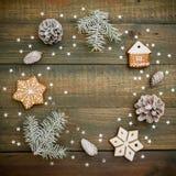 Marco del concepto de la Navidad o del Año Nuevo con los conos, el pan de jengibre y el abeto del pino en fondo de madera Endecha Fotos de archivo