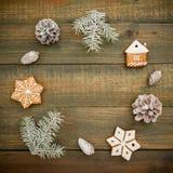 Marco del concepto de la Navidad o del Año Nuevo con los conos, el pan de jengibre y el abeto del pino en la tabla de madera Ende Imagenes de archivo