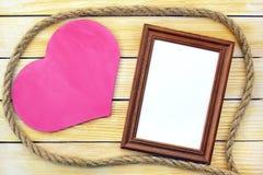 Marco del corazón y de la foto en el fondo de tableros de madera Fotografía de archivo