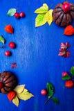 Marco del día de la acción de gracias Hojas, calabaza y pequeña manzana alrededor en fondo rústico azul de madera Visión superior Fotografía de archivo