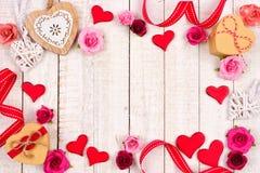 Marco del día de tarjetas del día de San Valentín de corazones, de flores, de regalos y de la decoración en la madera blanca Fotografía de archivo