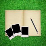 Marco del lápiz y de la foto con el libro en hierba verde Foto de archivo libre de regalías