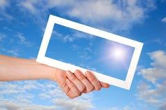 Marco del Libro Blanco en mano de la mujer en el cielo azul Foto de archivo