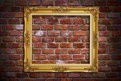 Marco del oro en la pared de ladrillo vieja Imagen de archivo libre de regalías