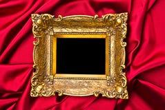 Marco del oro viejo en el satén rojo fotos de archivo