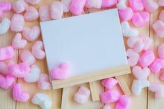 Marco en blanco blanco rodeado con los corazones rosados Fotografía de archivo