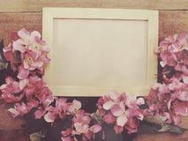 Marco en blanco de la foto con la decoración del ramo de la flor en viejo fondo de madera del grunge fotos de archivo libres de regalías