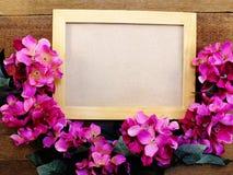 Marco en blanco de la foto con la decoración del ramo de la flor en viejo fondo de madera del grunge foto de archivo libre de regalías