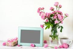 Marco en blanco de la foto con el ramo hermoso de flores de las rosas, de taza de café, de macarrones y de caja de regalo rosados imagenes de archivo
