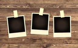 Marco en blanco de la foto en fondo de madera Fotografía de archivo
