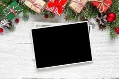 Marco en blanco de la foto de la Navidad con las ramas de árbol de abeto, las decoraciones y las cajas de regalo foto de archivo