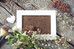 Marco en blanco de la foto y flores blancas sobre fondo de madera de la tabla imagen de archivo libre de regalías