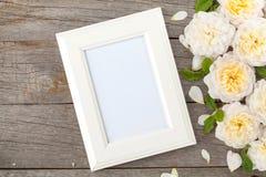Marco en blanco de la foto y rosas blancas Fotos de archivo libres de regalías