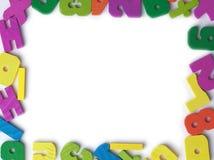 Marco en blanco de las figuras de madera coloreadas del juguete Foto de archivo