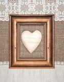 Marco envejecido con el corazón de madera en la arpillera Fotografía de archivo libre de regalías