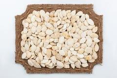 Marco figurado de la arpillera con las semillas de calabaza Foto de archivo