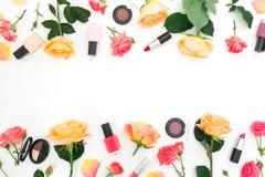 Marco floral con las rosas y los cosméticos femeninos en el fondo blanco Endecha plana, visión superior Fondo del blogger de la b foto de archivo