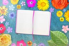 Marco hermoso de la flor con el cuaderno en el centro en fondo azul claro del adobe del grunge Composición floral del flowe de la stock de ilustración