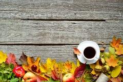 Marco inferior de las hojas del otoño, de las bellotas y de las manzanas rojas, verdes y amarillas con la taza de café o de té en foto de archivo