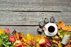 Marco inferior de las hojas rojas, verdes y amarillas del otoño, de las manzanas con la taza de café o del té con la palabra HOGA foto de archivo