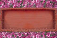 Marco metálico anaranjado en un fondo de flores rosadas Imagen de archivo