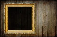 Marco negro de oro en una pared de madera Fotografía de archivo