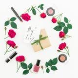 Marco redondo con las rosas, los cosméticos, la caja de regalo y la tarjeta con el ` escrito de la cita mi ` del amor en el fondo foto de archivo