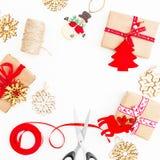 Marco redondo de la Navidad hecho de regalos, de guita, de juguetes y de tijeras en el fondo blanco Endecha plana, visión superio Foto de archivo