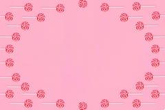 Marco redondo de piruletas con las rayas rojas y blancas en un fondo rosado imágenes de archivo libres de regalías