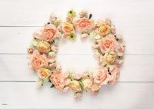 Marco redondo de rosas en un fondo de madera blanco con el balneario vacío Imagen de archivo libre de regalías