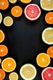 Marco redondo hecho de las naranjas, del pomelo y del limón aislados en fondo negro Endecha plana, visión superior Mezcla tropica Imagen de archivo
