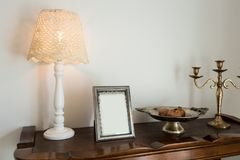 Marco retro de la decoración, de la lámpara y de la foto en el aparador fotografía de archivo
