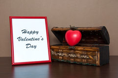 Marco rojo de la foto y pecho decorativo abierto con el corazón en la tabla de madera Fotografía de archivo libre de regalías
